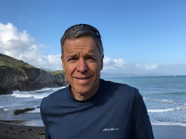 A photo of Brian Frank on a beach with water in the background