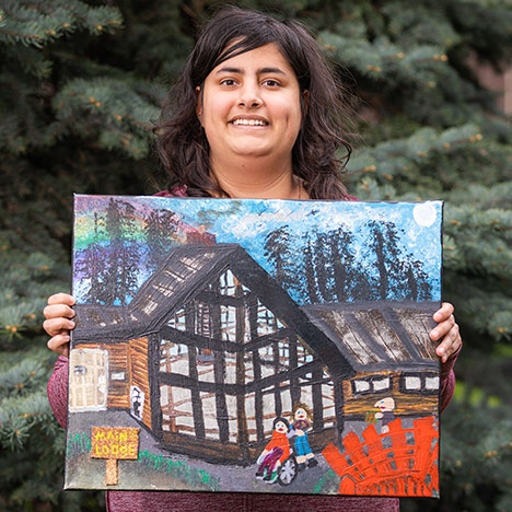 A participant of the National accessArts Centre's Indefinite Art Home Art holds up their creation
